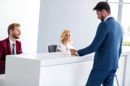Young receptionists attend handsome passenger