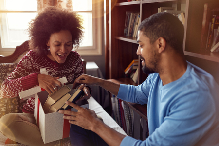 Happy Couple opening present together while celebrating Christmas at home Stock Photo