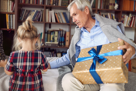 Giving Christmas gift on celebration time- grandfather with gift for his little granddaughter