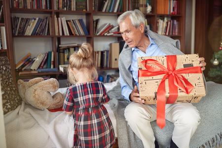 grandfather Giving present and celebration Christmas time with his granddaughter