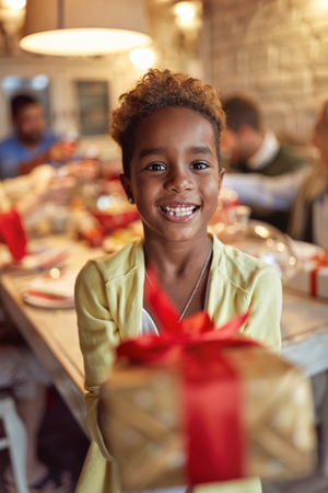Smiling Cute African girl celebration holiday and giving Christmas present Banco de Imagens