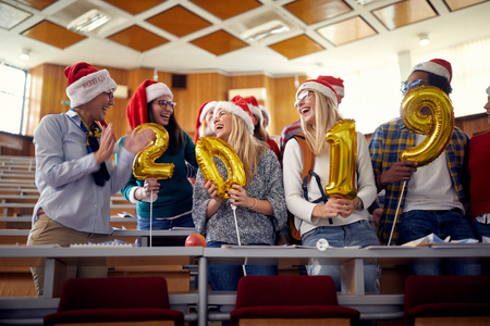 Group of happy colleagues in Santa hat having fun at new year celebration on university
