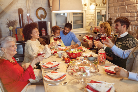 large happy family clinking glasses on Christmas dinner and enjoy in holidays Фото со стока