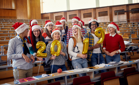 group of happy international students in Santa hat celebrating holiday