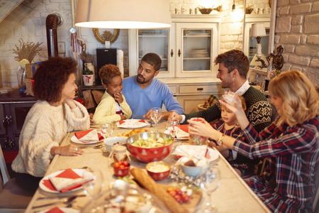 Smiling friends have fun at a family Christmas dinner Archivio Fotografico