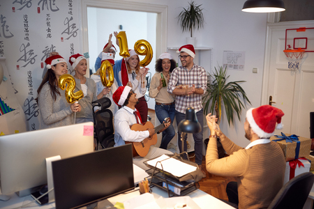 Smiling business workers have fun and dancing in Santa hat at Christmas party in office Stock Photo