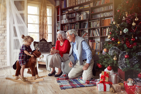 Cheerful grandparents and little happy girl playing together for Christmas Фото со стока
