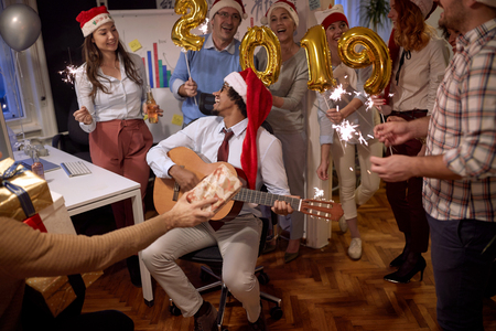 Successful business group people in Santa hat at Xmas party in office celebrating with song