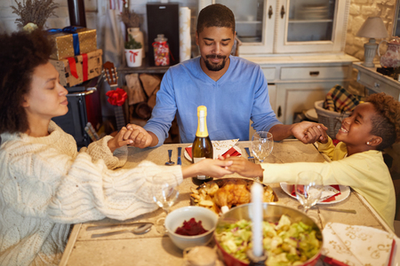 Christmas prayer – Young family dinner at home