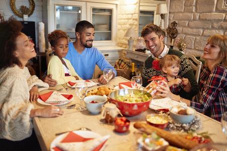 Sorridenti amici multietnici si divertono a una cena di Natale in famiglia