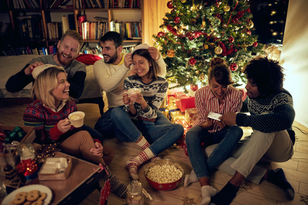 group of happy friends with gifts at a Christmas party