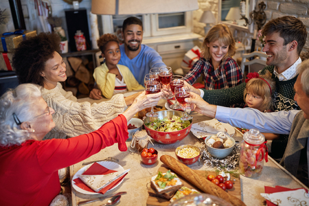 happy family and friends clinking glasses on Christmas dinner and enjoy in holidays