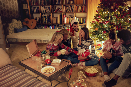 group of happy friends laughing and sharing Christmas gifts.