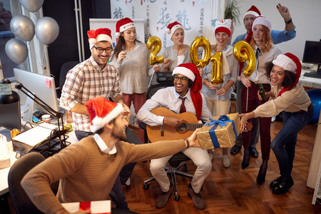 Smiling business workers have fun in Santa hat at Christmas party and exchange gifts in office Фото со стока