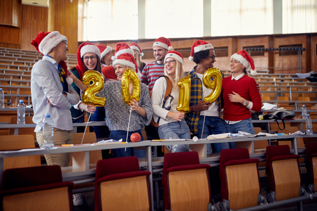 Happy Students friends in Santa hat holding 2019 golden balloons at New Year party on university Stock fotó