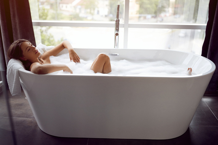 Attractive young girl lying in bathtub.