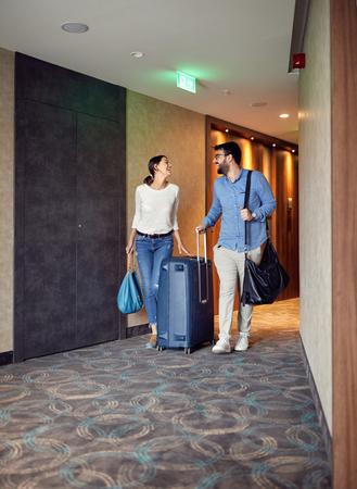 Hombre y mujer sonriente al llegar al vestíbulo del hotel con maleta