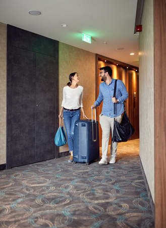 Smiling man and woman arriving at hotel lobby with suitcase