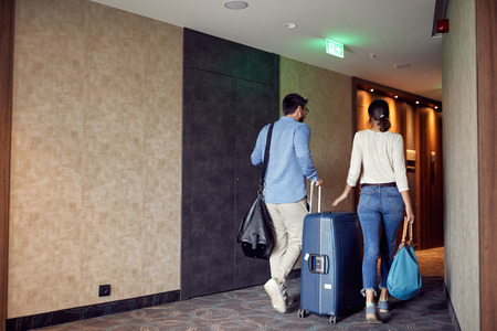 Happy couple arriving at hotel lobby with suitcase Standard-Bild