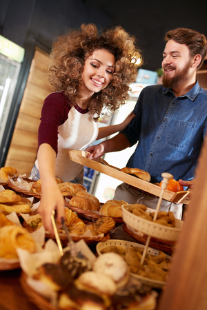 Saleswoman with man on break in pastry shop Stock Photo