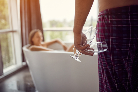 Enjoying a bath with champagne in a glasses –young man and woman relaxing together in the bathtub