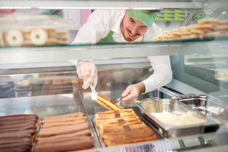Bakery worker very carefully taking out biscuit cake from showcase