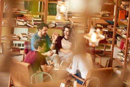 Deux jeunes hommes et femmes en conversation dans la bibliothèque Banque d'images