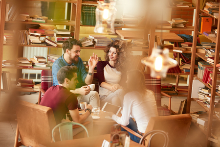 Twee jonge mannen en vrouwen in gesprek in bibliotheek Stockfoto