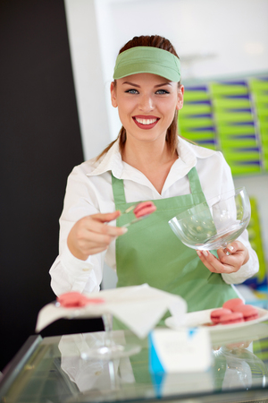 Smiling quite female worker in pastry shop taking macarons Stock Photo