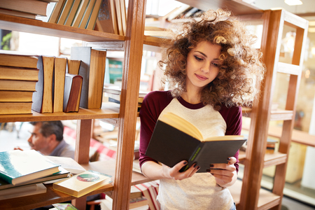 Curly female read book in library