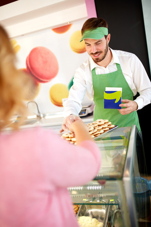 Confectionery salesman showing nice cookies on plate Stock Photo