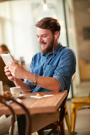 Young man in pleasant communication with cell phone in cafe