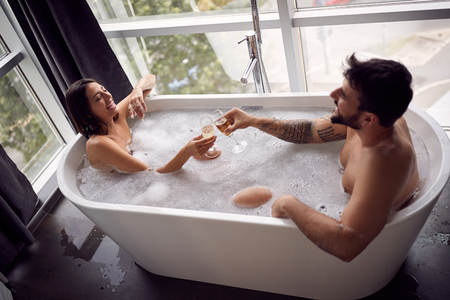 Sexy young couple enjoying and relaxing in the bathtub and drinking champagne