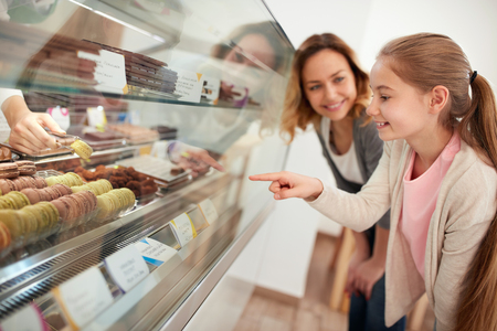 Girl with mother in pastry shop select macarons from showcase