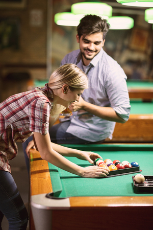 Young couple sorting balls for beginning billiard game