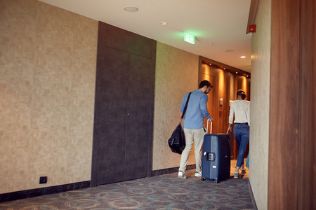 Young couple at hotel corridor upon arrival at vacation Stock Photo