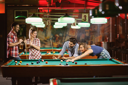 Friends enjoying in beer and playing billiard in bar