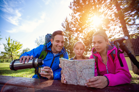 family hikers in forest with map