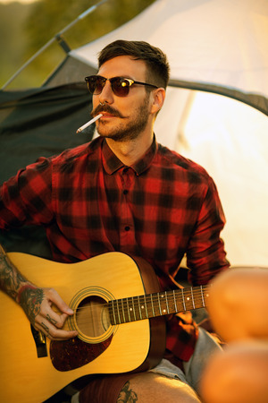 Portrait of hipster man with guitar on camping trip