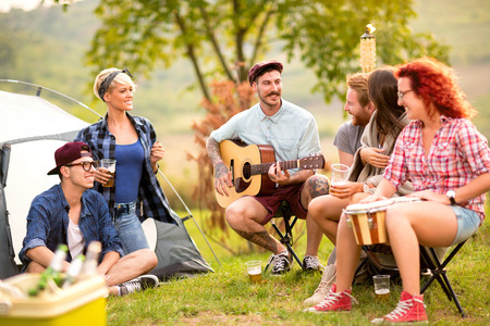 Three couples of young friends playing music and making jokes in front of tent in nature Stock Photo