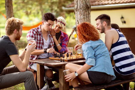 Youngsters thinks while playing chess in nature; Stockfoto