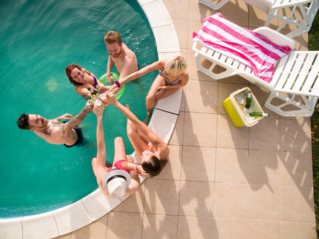 Top view of young people in swimming pool toasting with cold drinks Stock Photo