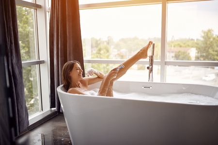 Young happy girl shaving her legs in the bath with foam Standard-Bild