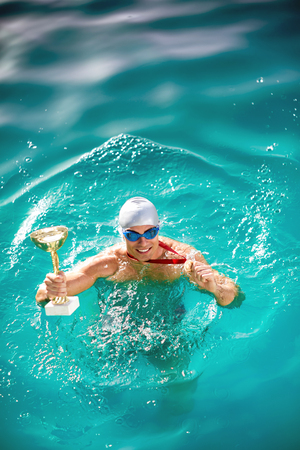 Winning Swimmer in swimming pool with
