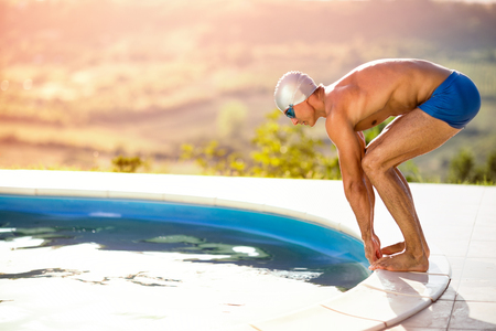 Young muscular swimmer in low position on side of swimming pool ready to jump in water