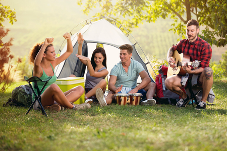 Happy young people having fun with music of drums and guitar on camping trip