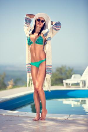 Trendy girl in swimsuit posing by pool