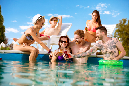 Three young male and female pairs toasting with bottles of drink in swimming pool at summer Stock Photo