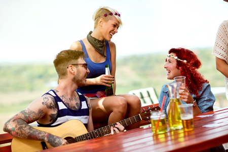Young perky girls drinks beer and talks while tattooed hipster guy plays guitar in restaurant in nature