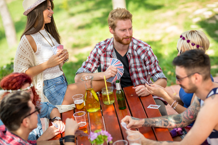 Playing cards outdoor with friends and drinks in nature is enjoyment for young people